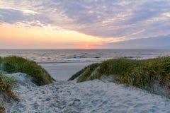 在美丽的海滩的日落与在Henne子线,日德兰丹麦附近的沙丘风景 免版税库存图片