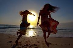 在美丽的海滩的母亲和女儿跳舞。 免版税库存图片