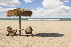 在美丽的海洋沙子的二把海滩睡椅和伞 免版税库存图片