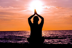 在美丽的海滩的女性瑜伽lotos剪影在日落期间 免版税库存照片