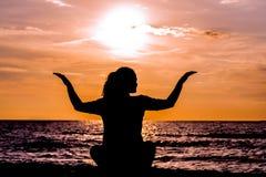 在美丽的海滩的女性瑜伽lotos剪影在日落期间 免版税库存图片