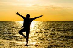 在美丽的海滩的女性瑜伽vriksasana剪影在日落期间 免版税库存照片