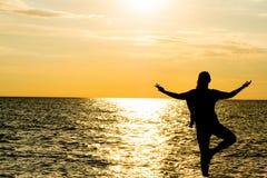 在美丽的海滩的女性瑜伽vriksasana剪影在日落期间 库存照片