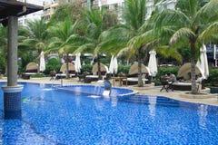 在美丽的游泳池附近的放松:有pi的豪华沙发 免版税库存照片