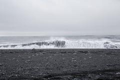 在美丽的火山的黑沙子的波浪靠岸 库存图片