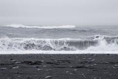 在美丽的火山的黑沙子的波浪靠岸 免版税库存照片