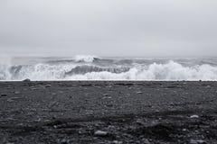 在美丽的火山的黑沙子的波浪靠岸 免版税库存图片