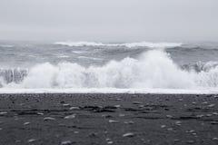 在美丽的火山的黑沙子的波浪靠岸 图库摄影