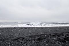 在美丽的火山的黑沙子的波浪靠岸 库存照片