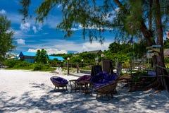 在美丽的热带海滩的竹椅子 免版税库存图片