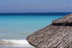 在美丽的热带海滩的秸杆伞 在海和山照片附近的遮阳伞 库存图片