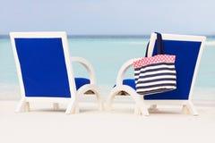 在美丽的热带海滩的空的椅子 库存照片