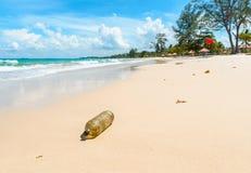 在美丽的热带海滩的老塑料瓶 免版税库存照片