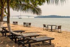 在美丽的热带海滩的轻便折叠躺椅 免版税库存照片