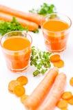 在美丽的玻璃、裁减橙色菜和绿色荷兰芹的红萝卜汁在白色木背景 饮料新鲜的桔子 接近的u 免版税库存照片