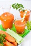 在美丽的玻璃、裁减橙色菜和绿色荷兰芹的红萝卜汁在白色木背景 饮料新鲜的桔子 接近的u 免版税图库摄影