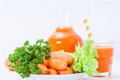 在美丽的玻璃、裁减橙色菜和绿色荷兰芹的红萝卜汁在白色木背景 饮料新鲜的桔子 接近的u 免版税库存图片