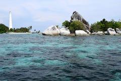 在美丽的珊瑚岩石后的白色灯塔和与好的蓝色海的绿色灌木 库存图片
