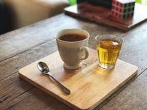 在美丽的白色杯子和热的茶玻璃,在木盘子的不锈的匙子的无奶咖啡 免版税库存图片