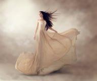 在美丽的米黄流动的薄绸的礼服的时装模特儿 图库摄影