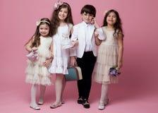 在美丽的经典葡萄酒衣物打扮的一个小组愉快的孩子,隔绝在桃红色背景 图库摄影