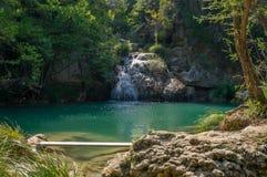 在美丽的绿色polylimnio瀑布的长凳 免版税库存图片