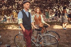 在美丽的老服装和帽子的年轻夫妇有葡萄酒的骑自行车去节日减速火箭的巡航的 免版税库存图片