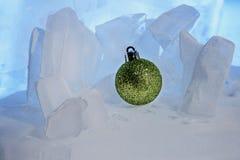 在美丽的蓝色冰的圣诞节绿色发光的球 免版税库存图片