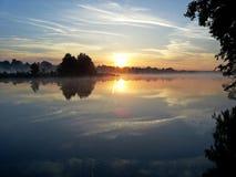 在美丽的鸟云彩之上颜色及早飞行金子早晨本质宜人的平静的反映上升海运一些星期日 日出 免版税库存图片