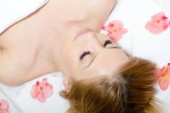 在美丽的年轻可爱,豪华白肤金发的妇女的特写镜头画象与眼睛的温泉做法的关闭了围拢由桃红色花 免版税库存图片