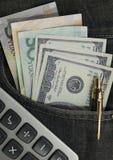 在美元的概念计算器和在后面牛仔裤的中国元装在口袋里 免版税库存照片