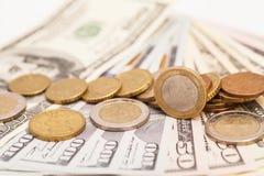 在美元笔记的欧洲硬币 库存照片