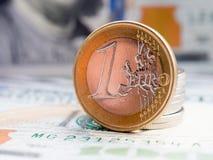 在美元背景的一欧元 库存照片