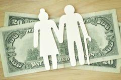 在美元钞票的纸年长夫妇保险开关-浓缩的退休金 图库摄影