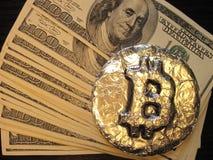 在美元钞票的Bitcoin 真正的硬币在一百元钞票作为热的价格或交换率的标志 库存照片