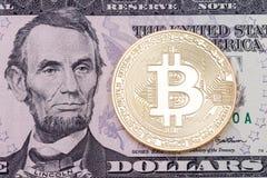 在美元钞票背景的金黄cruptocurrency bitcoin 免版税库存照片