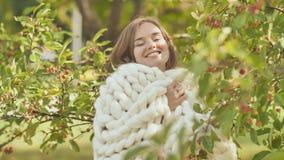 在美利奴绵羊的格子花呢披肩包裹的一个微笑的女孩在一棵樱桃树中间在一个公园在早期的秋天 股票视频