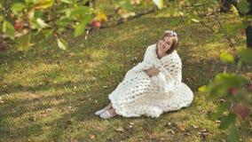 在美利奴绵羊的格子花呢披肩包裹的一个微笑的女孩坐在一个城市公园在早期的秋天 股票录像