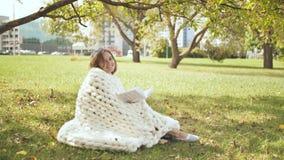 在美利奴绵羊的格子花呢披肩包裹的女孩在城市公园读一本书 股票视频
