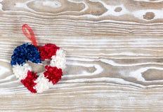 在美国传统颜色的心脏花圈在白色木板 库存照片