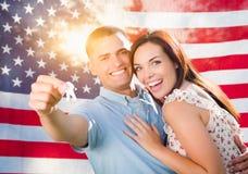 在美国国旗前面的军事夫妇藏品议院钥匙 免版税库存图片