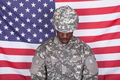 在美国国旗前面的军队战士 免版税库存照片