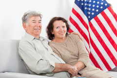 在美国国旗前面的愉快的资深夫妇就座 免版税库存照片