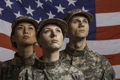 在美国国旗前面被摆在的三位战士,水平 免版税图库摄影