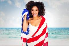 在美国国旗包裹的俏丽的女孩的综合图象微笑对照相机 免版税图库摄影