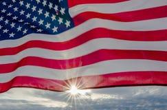 在美国国旗后的太阳火光 免版税库存照片