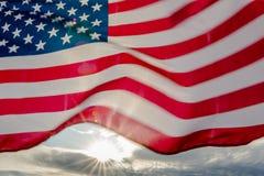 在美国国旗后的太阳火光 库存照片