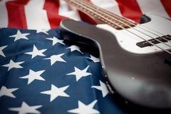 在美国国旗背景的葡萄酒低音吉他 库存照片