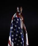 在美国旗子包裹的美国黑人的运动员 库存照片