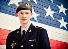 在美国旗子墙壁前面的美国十几岁的男孩 库存图片